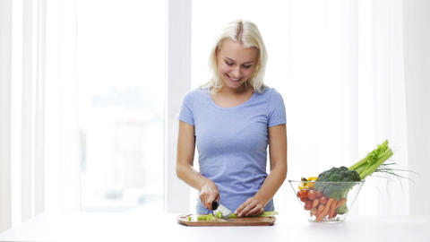 smiling young woman chopping celery at home Footage