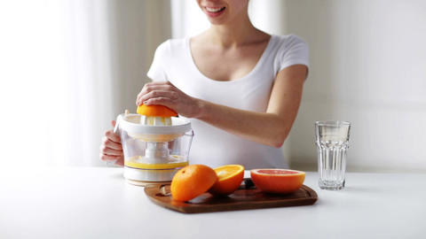 woman with squeezer squeezing orange juice at home Live Action