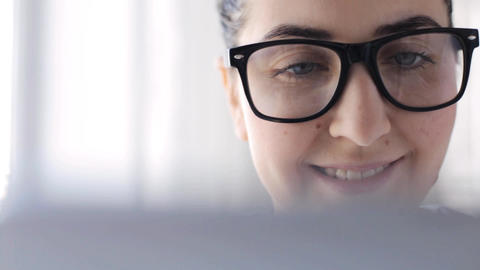 young woman in eyeglasses with tablet pc at home Live Action