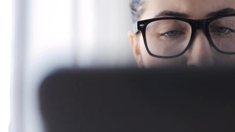 young woman in eyeglasses with laptop at home Live Action