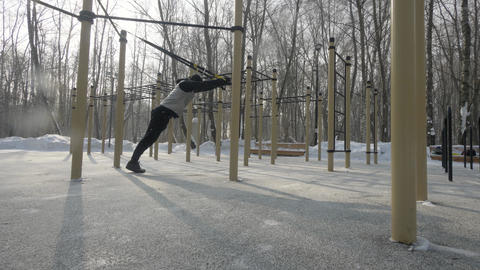 Fitness man exercising with sport straps on winter sport ground. Sport lifestyle Footage