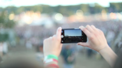Young adult female photographing at music festival ビデオ