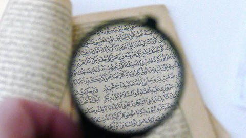 magnifying glass and examine the old Ottoman Turkish book Footage