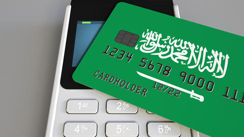 Payment or POS terminal with credit card featuring flag of Saudi Arabia. Retail Footage