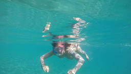 Girl approaching, swimming and snorkeling on a beach with turquoise waters, slow GIF