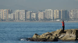 Fisherman throwing the canne a sunny day with a mediterranean city at background Footage