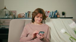 Nice Adult Woman is Using App on Smartphone Sitting on Sofa in a Cozy Room フォト