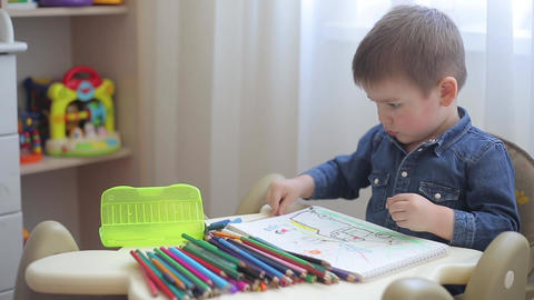 A small child learns to draw with colored pencils on paper Footage