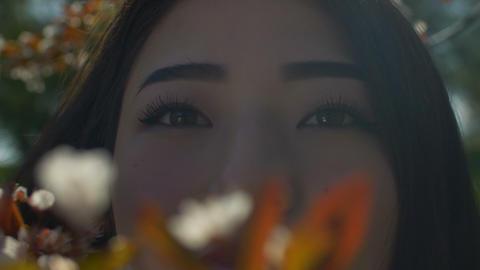 Portrait of elegant asian woman in blooming tree Footage