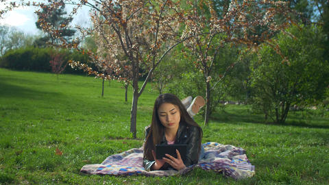 Smiling young woman laying on lawn with tablet pc Footage