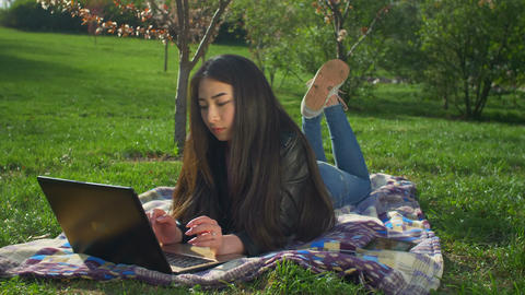 Asian girl working with her notebook lying on lawn Footage
