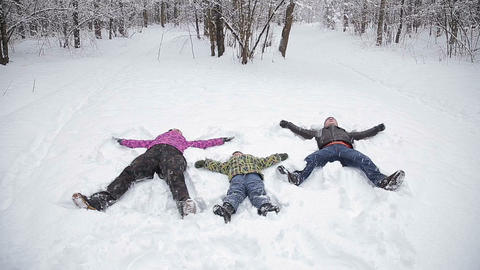 Family making snow angel, laying down on snow Footage