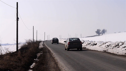 Cars which run on a road across a field covered with snow 3 Footage