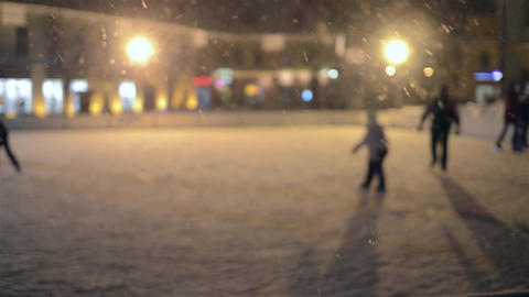 Snow settles on skating rink arranged in the amusement park that few people thro Footage