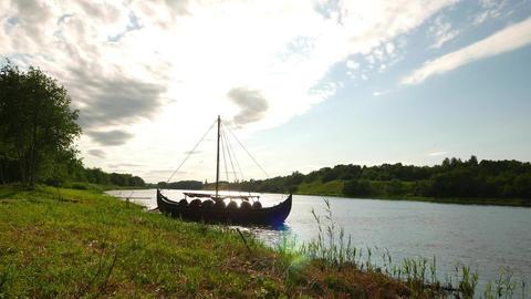 Viking longship moored at wild river coast, glide camera move closer Footage