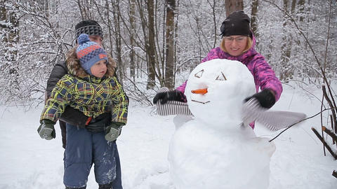 Happy family of three making a snowman Footage