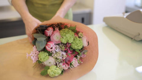 florist wrapping flowers in paper at flower shop Footage