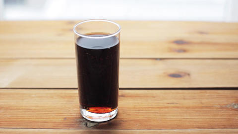 glass of lemonade or soda drink on wooden table Footage