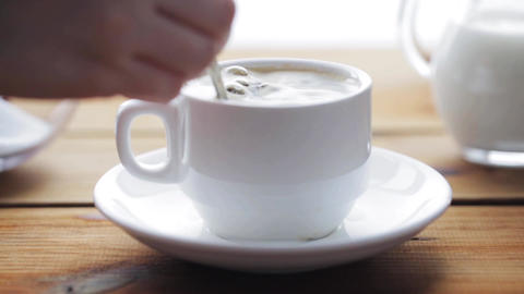 hand pouring sugar by teaspoon into coffee cup Footage