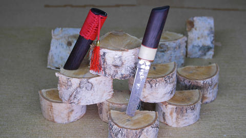 Japanese samurai knife with red tassel moving on wind on wooden stumps Footage