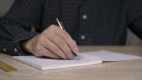 Male hand writing in notebook. Man using ballpoint pen for writing in diary Live Action