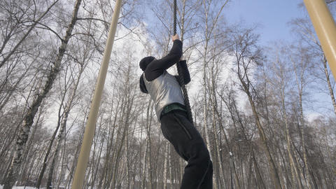 Strong man climbing on rope during outdoor workout on sport ground Footage