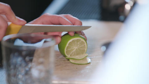Close-up of Hands Slicing a Lime in the Kitchen Footage