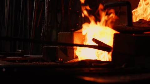 Closeup of a blacksmith fanning the flames of the furnace, using the tools Footage