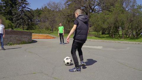 Boys plays football in summer park Footage