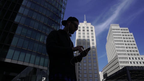 Silhouette Of Man In Earphones Listening To Music On Smartphone On City Street Footage