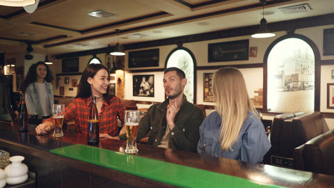 Young people are talking at bar counter over beer when couple of their friends Footage