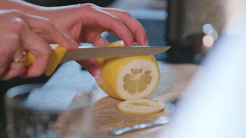 Close-up of Hands Slicing a Lime in the Kitchen GIF
