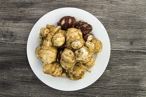 Jerusalem artichoke is very useful in terms of health, in the plate Jerusalem Photo