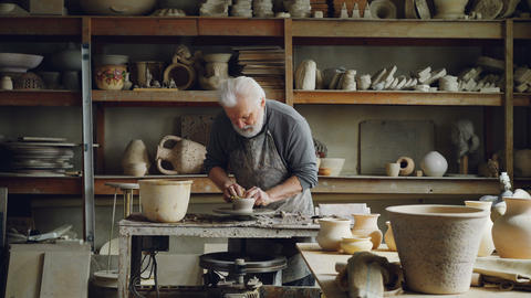 Experienced ceramist is creating utensils from clay on potter's wheel in Footage