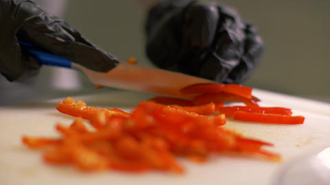 Chef hands cutting red bulgarian pepper into pieces for cooking vegetable salad Footage