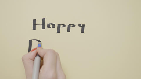 Young female hands writing happy birthday on a paper with black pen Footage