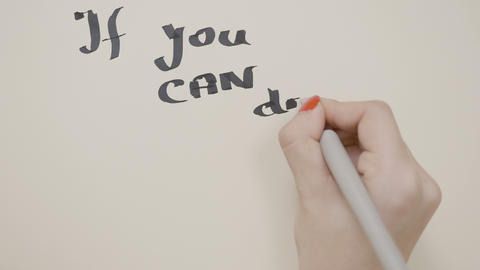 Young teenager girl hands writing motivational quote if you can dream it you can Footage