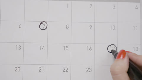 Female hands with red manicure circling and crossing dates on a calendar drawing Footage