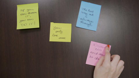 Young depressed woman sticking handwritten post it with motivational quotes on Footage