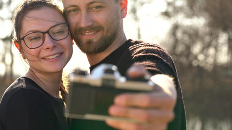 Young couple in love taking photo of themself on a film camera. Slow motion Footage