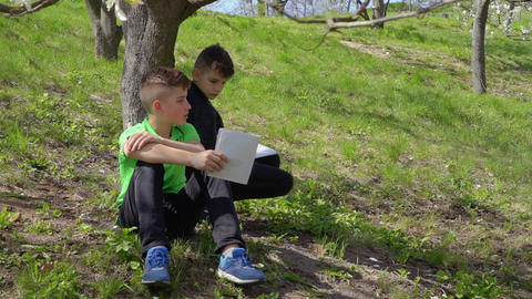 Two boys discusses school homework sitting under the tree in park Footage