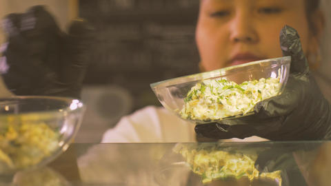 Woman putting bowl with salad in shop window restaurant for business lunch Live Action
