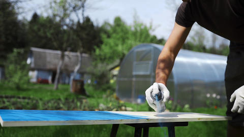 Man's hand in working glove sprays paint with spray can to the wooden surface Live Action