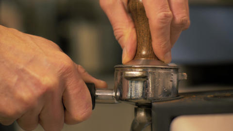 Close up barista pressing ground coffee before preparation in coffee shop Footage