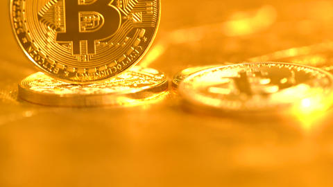 Bitcoin coins on a shiny golden background GIF