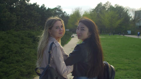 Pretty multiracial girls turning back smiling in park Footage