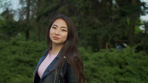 Portrait of beautiful asian girl smiling in park Footage