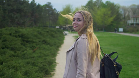 Joyful blonde girl turning back and smiling in park Footage