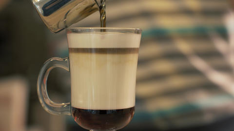 Barista pouring coffee in glass cup with milk for preparing latte in cafeteria Footage