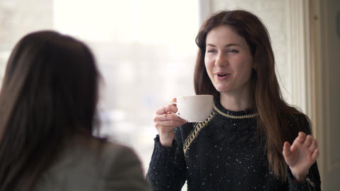 Young woman drinking coffee and talking with friend during meeting in cafe Footage